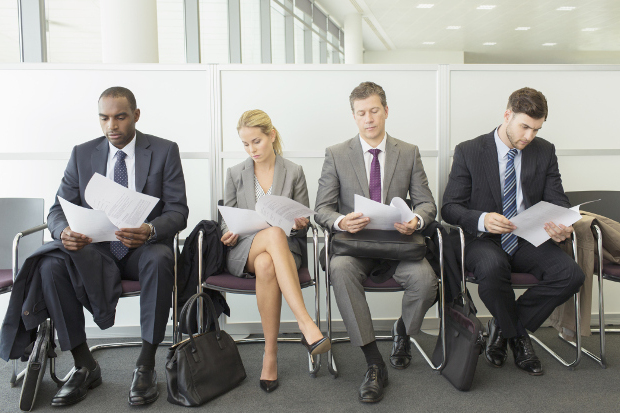 A line of professionals sitting in chairs waiting for an interview