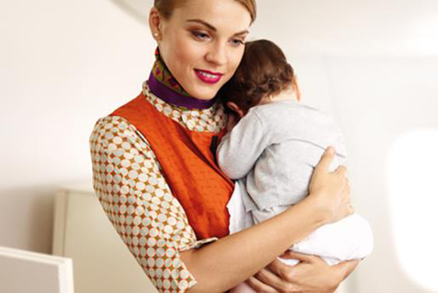 An Etihad Flying Nanny holding a young baby