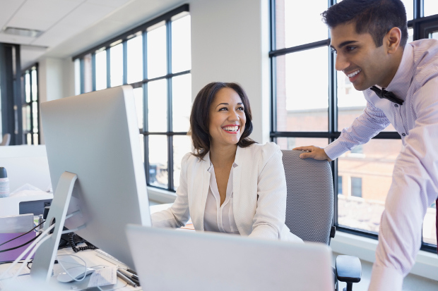 two office workers looking at computer and smiling