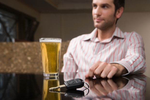 A man sitting at a table with a beer and car keys