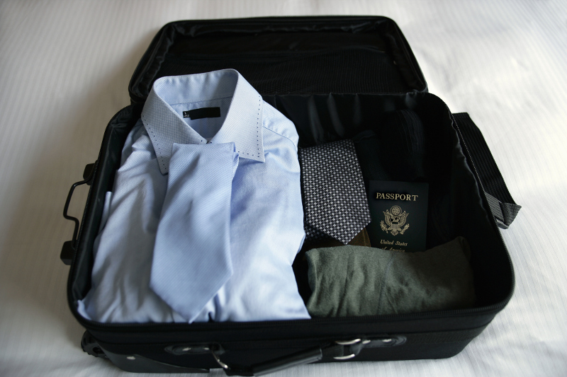 A carry-on bag packed with business attire