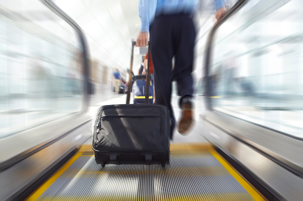 Close up of a man carrying a carry-on