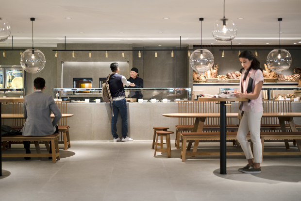 Travellers ordering and eating in the dining area of Cathay Pacific's The Pier