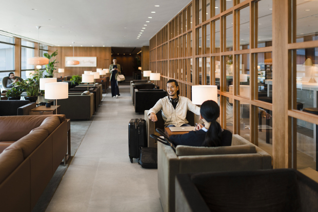 Two travellers sitting in the lounge area of Cathay Pacific's The Pier