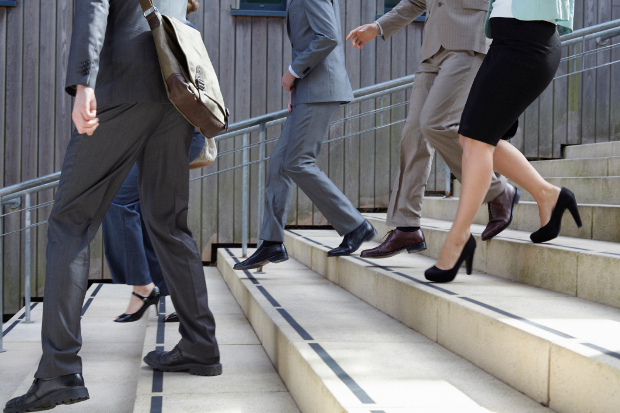 A close shot of a group of business people walking down the stairs