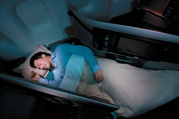 A man sleeping in one of Cathay Pacific's lie-flat business class seats