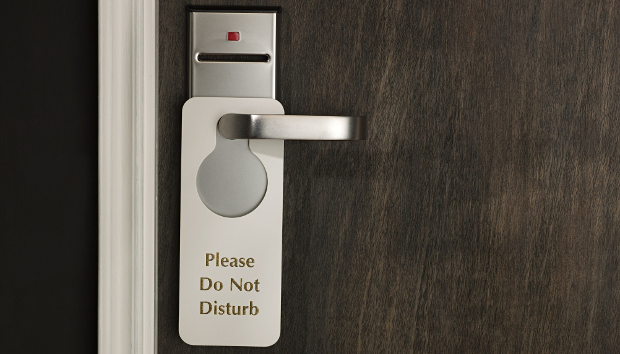 A do not disturb sign hanging on a hotel room door handle