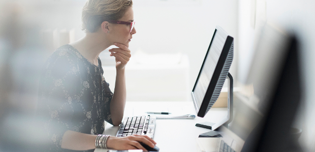 A young woman thoughtfully reading something on her computer screen