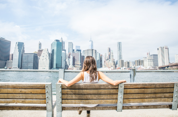 A woman looking at the New York skyline from a park bench