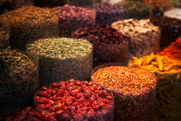 Rows of containers holding colourful spices at a market