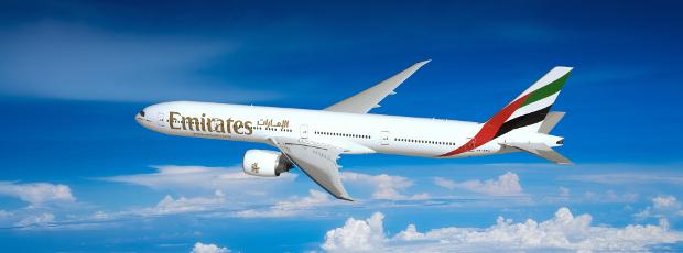 An Emirates B777-300er flying through the sky