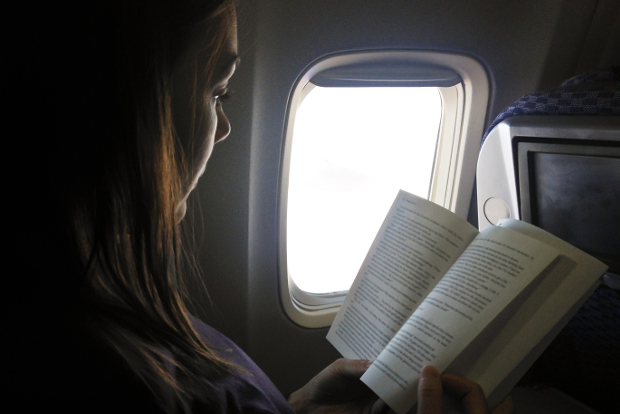 A woman reads a book while travelling on a plane.