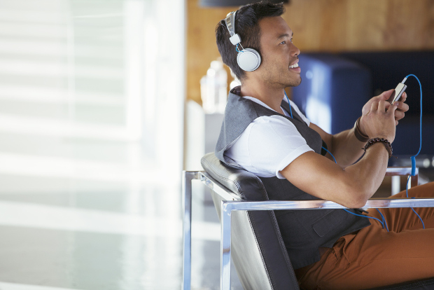 A young businessman listens to a podcast.