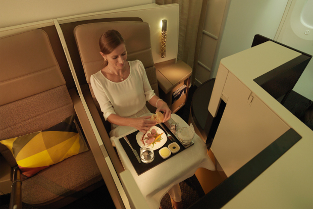 Woman eating in an Etihad business class studio seat