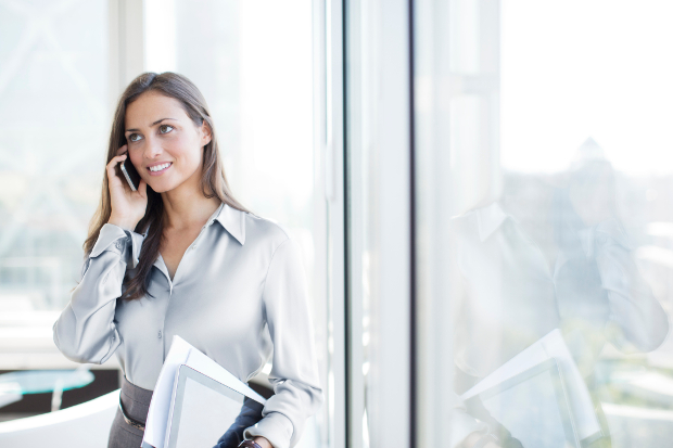 Happy female office worker on the phone