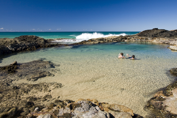 Two people relaxing in natural pools overlooking the ocean at Fraser Island