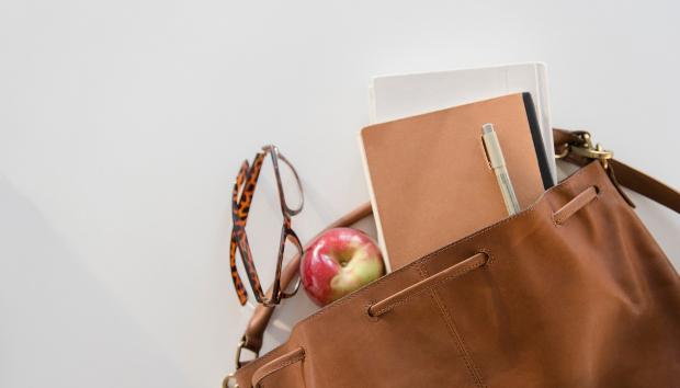 A women's handbag with a few things peeking out, including an apple