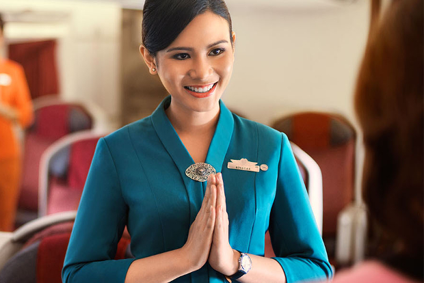 A flight attendant greeting a passenger