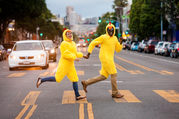Two people crossing the road in chicken costumes