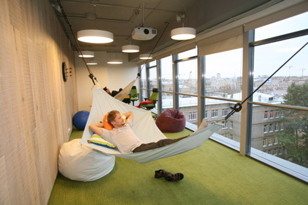 One of the offices in google with employees laying on hammocks and enjoying the city views