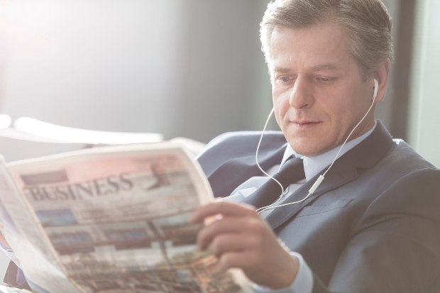 A businessman reading a newspaper with headphones on