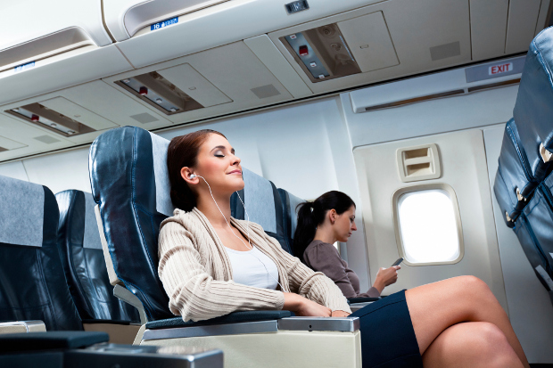 Woman with headphones resting on a plane