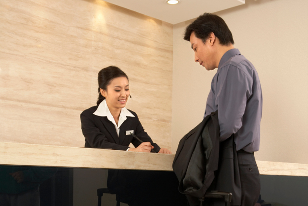 A hotel concierge talking to a businessman