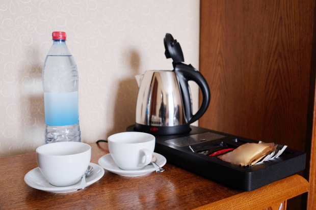 A hotel kettle and other in-room amenities