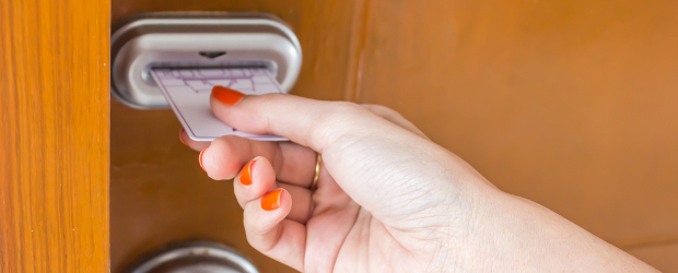 close up of a woman putting a hotel card key in her door lock