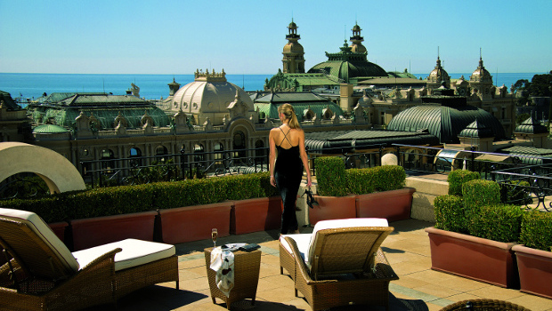 A woman enjoying a view of Monaco from the top of the Hotel Monaco