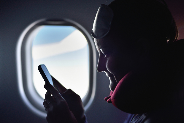 A woman looking at her phone during a flight