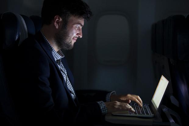 A man using a laptop during a flight