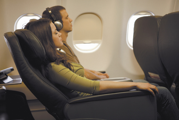Woman relaxing in reclining airplane seat