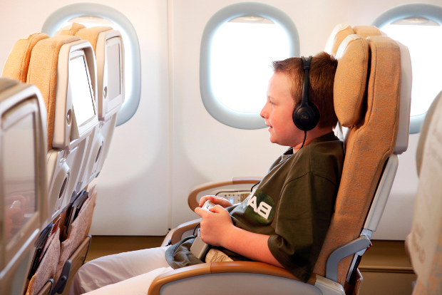 A young passenger playing video games with his in-flight entertainment system