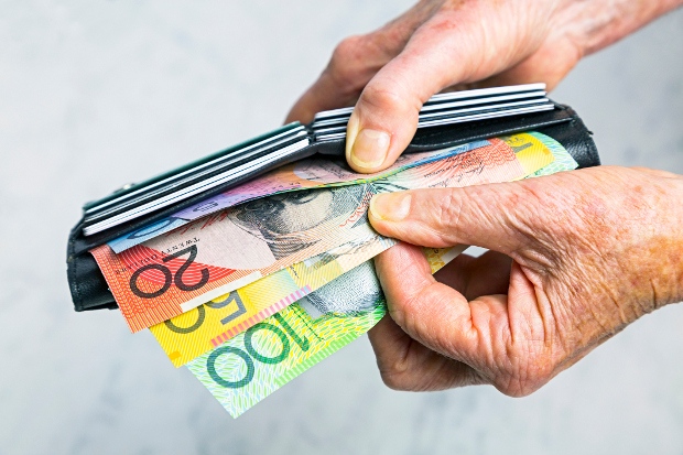 A person holding a wallet with some visible Australian notes