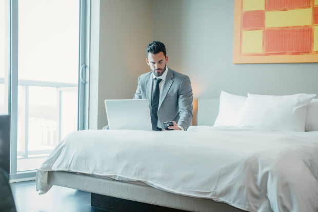 A man sitting on a hotel bed checking his phone with his laptop open