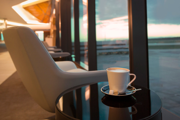 A close up of a seat looking out the window with a cup of coffee sitting on a table next to it