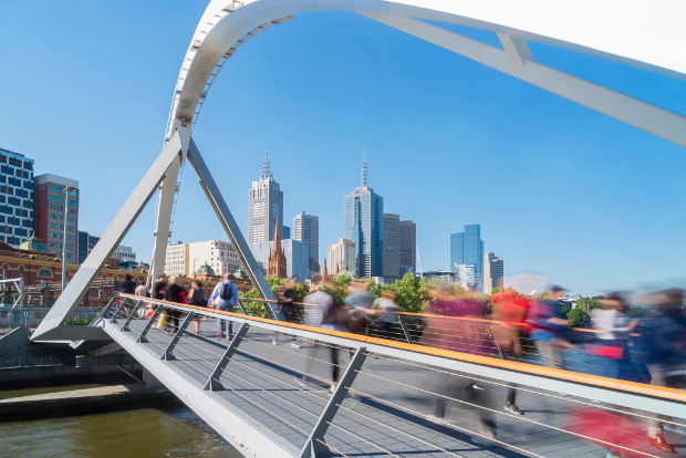 People walking over a pedestrian bridge in Melbourne toward the city