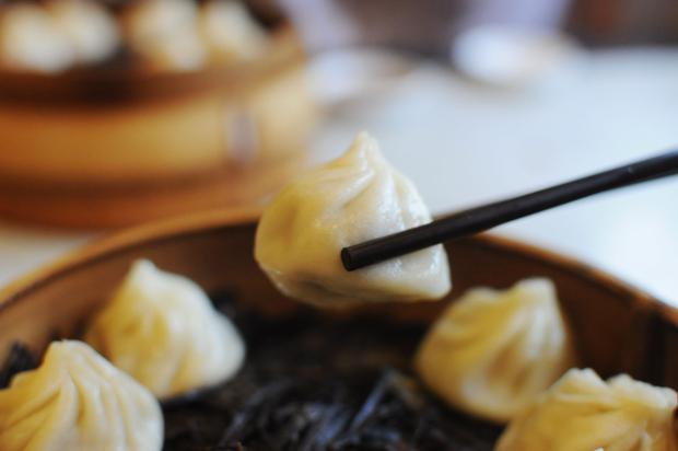 A chopstick holding a small dumpling
