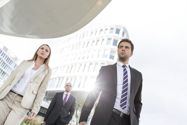 Three young business people walking amongst tall buildings