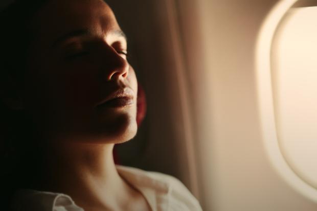A woman sleeping on a plane