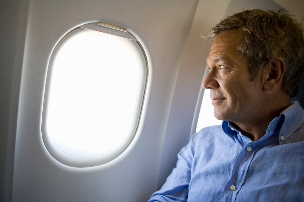 A man looking out the window of an airplane with a slight smile
