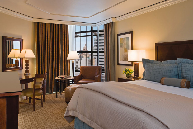 The interior of one of the rooms of the Omni Austin hotel looking out to the surrounding city