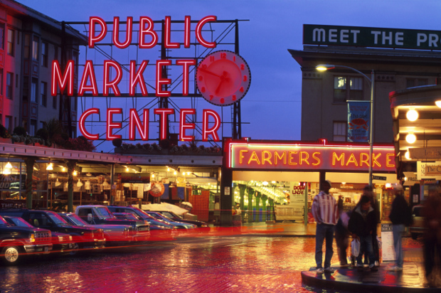 "A night view of the pike place market ""public market centre\"" sign lit up."