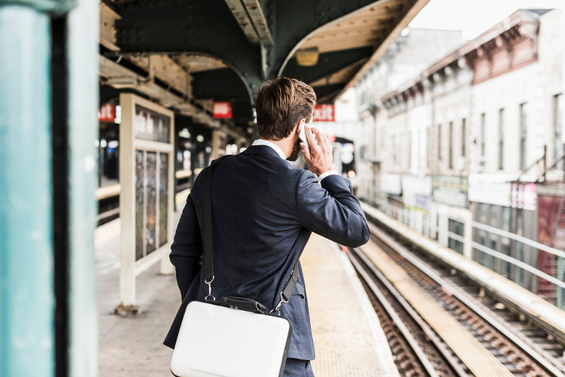 A business man on his phone waiting for the train