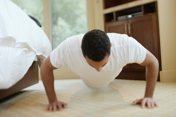 A man doing push ups next to a bed