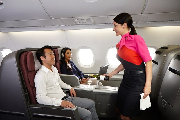 Passenger being served champagne in a business class seat