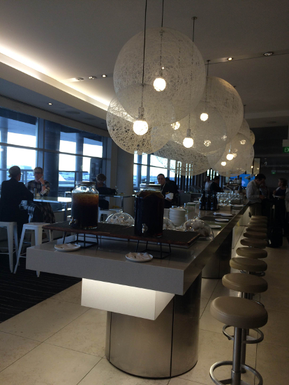 Looking down a long buffet table with people in the background in the Qantas Business Lounge