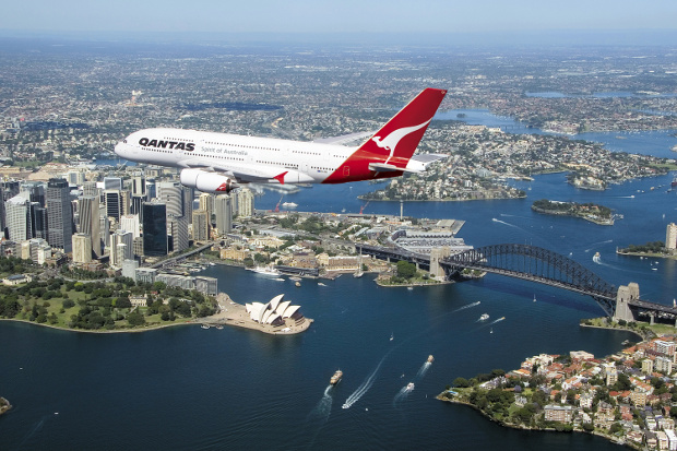 A Qantas plane flying over Sydney with the Harbour Bridge and Opera House in the background