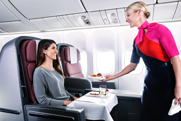 Flight attendant serves a female passenger a plate of food in business class